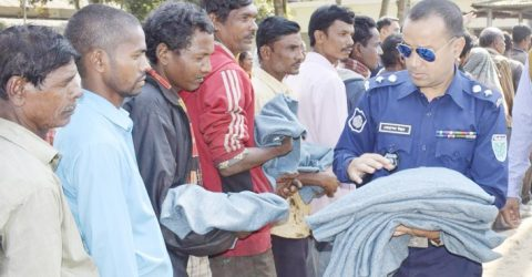 Habiganj Police Super Mohammad Ullah stands beside poor people